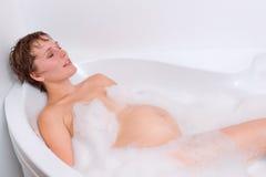 Gravida kvinnan är avslappnande i badet Royaltyfria Bilder
