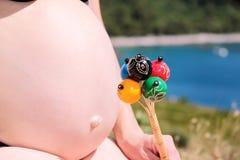 Gravida kvinnan är den hållande klassiska färgrika pladderBaby Bellleksaken på den gravida buken Den framtida mamman och förälder Royaltyfria Bilder