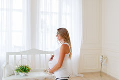 Gravida kvinnan är i det ljusa rummet Royaltyfri Bild