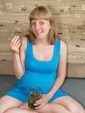 Gravida kvinnan äter knipan på ett golv Toxicosis arkivbilder