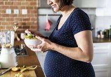 Gravida kvinnan äter sund mat royaltyfria foton