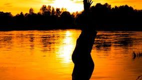 Gravida kvinnan dansar på solnedgång på flodbakgrund arkivfilmer
