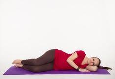Gravida kvinnan gör yoga Arkivbilder