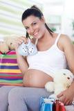 Gravida kvinnan har köpt saker för ditt behandla som ett barn Royaltyfri Bild