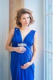 Gravida kvinnan i blått klär nära fönster leende Fotografering för Bildbyråer