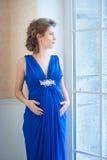 Gravida kvinnan i blått klär nära fönster Prifile Fotografering för Bildbyråer