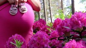 Gravida kvinnan i klänning rymmer händer på buken på naturlig bakgrund av rhododendron arkivfilmer