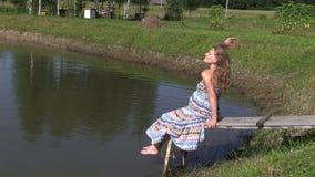 Gravida kvinnan i lång klänning sitter på träbron nära dammet arkivfilmer
