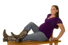 Gravida kvinnan i purpurfärgad skjorta och kängor sitter på bänk Royaltyfri Foto