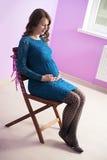 Gravida kvinnan i sapphirineklänning sitter på stolen royaltyfri bild