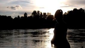 Gravida kvinnan klappar hennes buk på bakgrundssolnedgång på floden lager videofilmer