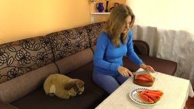 Gravida kvinnan klippte vattenmelon och den pålagda tabellen i vardagsrum Royaltyfri Fotografi