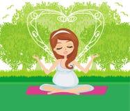 Gravida kvinnan kopplar av att göra yoga Royaltyfri Foto