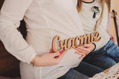 Gravida kvinnan kramar hennes buk med dottern Lycka för handhållinskrift royaltyfria bilder