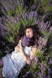 Gravida kvinnan ligger i ett fält av blommor Royaltyfri Bild