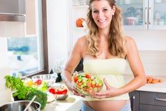 Gravida kvinnan med behandla som ett barn buken som äter sund sallad Arkivbilder