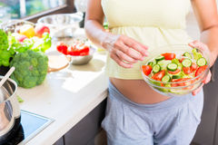 Gravida kvinnan med behandla som ett barn buken som äter sund sallad Royaltyfria Foton