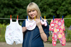 Gravida kvinnan med behandla som ett barn kläder behandla som ett barn kläderklädstrecket Royaltyfria Foton