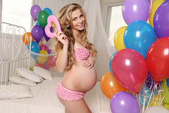 Gravida kvinnan med blont hår som poserar med färgrika luftballons och, dekorerar hjärta Arkivfoto