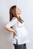 Gravida kvinnan med starkt smärtar att massera henne tillbaka Fotografering för Bildbyråer