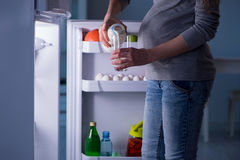 Gravida kvinnan nära kylen som söker efter mat och mellanmål på natten Royaltyfria Foton