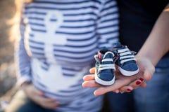Gravida kvinnan och hennes make rymmer bytena, en annan hand på hennes gravida tomach Arkivbild
