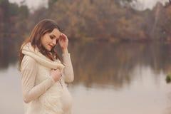 Gravida kvinnan på utomhus- höst går, det hemtrevliga varma lynnet Royaltyfri Fotografi