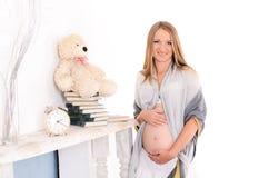 Gravida kvinnan räcker kramar försiktigt en mage royaltyfri foto