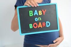 Gravida kvinnan rymmer en färgad text för behandla som ett barn ombord på svart tavla Arkivbilder