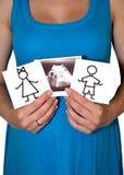 Gravida kvinnan rymmer teckningar av flickan och pojken och en bild av ultraljudsundersökningen av barnet royaltyfri bild