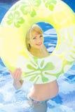 Gravida kvinnan simmar med den gröna rubber cirkeln arkivbilder