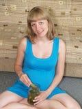 Gravida kvinnan sitter på ett golv med en can av knipor Toxico arkivfoto