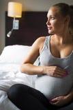 Gravida kvinnan sitter på säng med hennes händer på buken Arkivfoton