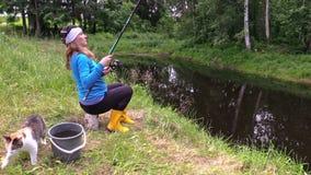 Gravida kvinnan sitter på stubbe och fångar fisken med den gulliga strimmig kattkatten arkivfilmer