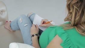 Gravida kvinnan skriver i en dagbok, medan ligga på soffan stock video