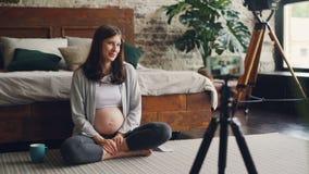 Gravida kvinnan som den kvinnliga bloggeren antecknar videoen för anhängare om havandeskap, flicka, sitter på sovrumgolv stock video