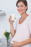 Gravida kvinnan som dricker ett exponeringsglas av, mjölkar royaltyfria foton