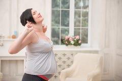 Gravida kvinnan som förväntar henne, behandla som ett barn Arkivfoton