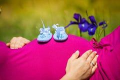 Gravida kvinnan som ligger på ett gräs med, behandla som ett barn skor på hennes buk Arkivbilder