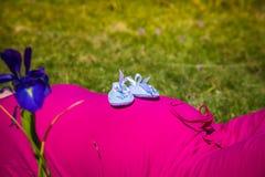 Gravida kvinnan som ligger på ett gräs med, behandla som ett barn skor på hennes buk Arkivfoto