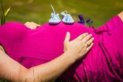 Gravida kvinnan som ligger på ett gräs med, behandla som ett barn skor på hennes buk Arkivbild
