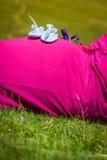 Gravida kvinnan som ligger på ett gräs med, behandla som ett barn skor på hennes buk Arkivfoton