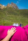 Gravida kvinnan som ligger på ett gräs med, behandla som ett barn skor på hennes buk Royaltyfri Foto