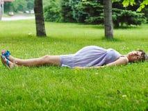 Gravida kvinnan som ligger på gräset royaltyfri foto