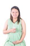 Gravida kvinnan som rymmer hennes gravida buk och, får ett exponeringsglas av mil Royaltyfri Foto