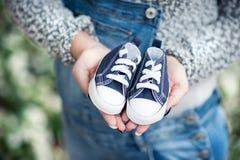 Gravida kvinnan som rymmer små skor för henne, behandla som ett barn Arkivbilder