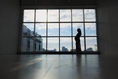 Gravida kvinnan står vid fönstret Arkivbild