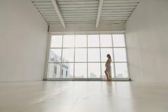 Gravida kvinnan står vid fönstret Fotografering för Bildbyråer