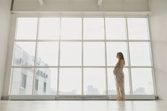 Gravida kvinnan står vid fönstret Royaltyfri Fotografi