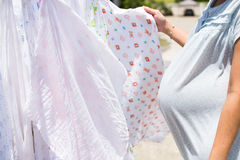Gravida kvinnan torkar torkdukeblöjan i solen Royaltyfri Fotografi